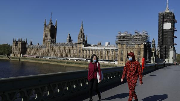 People wear masks as they walk near Britain's Houses of Parliament as it goes back to work, London, Tuesday, April 21, 2020.