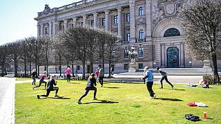 People exercise on a lawn, keeping distance amid the coronavirus disease (COVID-19) outbreak, outside the old parliament building in central Stockholm, Sweden, Tuesday, April
