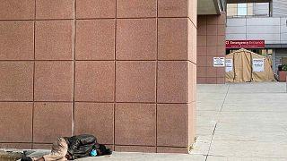 شخص بلا مأوى ينام أمام مركز طبي وسط تفشي جائحة فيروس كورونا، 21 أبريل 2020 ،لوس أنجلوس، كاليفورنيا