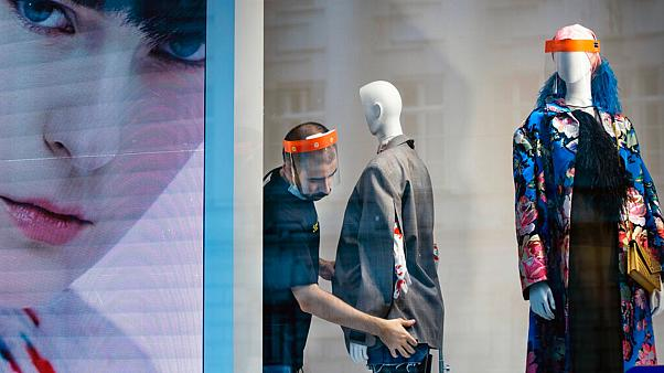 A fashion shop employee wearing a face mask adjusts a mannequin in Moscow, Russia, Tuesday, April 14