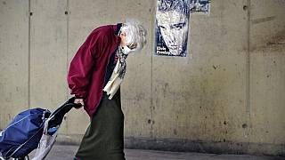 An elderly woman drags a shopping trolley, backdropped by an Elvis Presley poster, at a market place in Bucharest, Romania