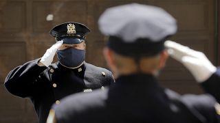 عنصران من حرس الشرف في شرطة نيويورك يؤديان التحية خلال تأبين قائد في الشرطة توفي بعد إصابته بكورونا