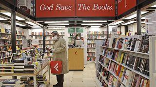 Un hombre ojea un volumen en una librería de Roma