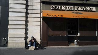 Бездомный сидит у закрытой кондитерской в Париже.