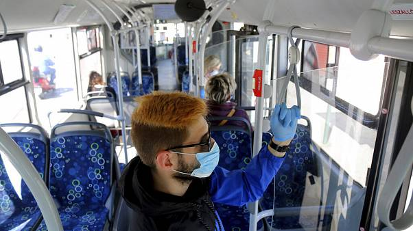 A man uses facial mask and gloves while riding on a public bus as a preventive measure against the coronavirus in Miskolc, Hungary, April 23, 2020
