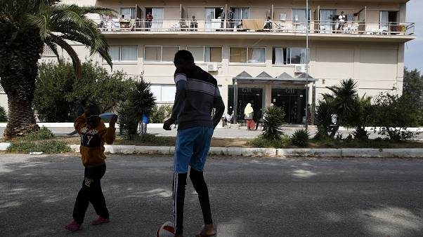 Migrant boys play with a ball outside a hotel in Kranidi town about 170 kilometers (106 miles) southwest of Athens, Tuesday, April 21, 2020