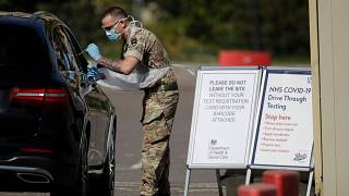 A soldier gives does a COVID-19 test at a drive-through testing centre at Chessington World of Adventures, Greater London