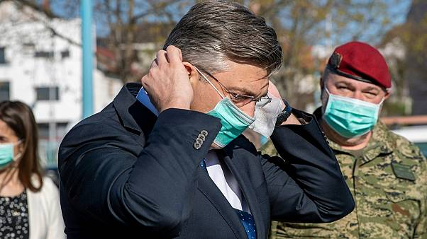 Croatia's Prime Minister Andrej Plenkovic puts on a protective mask on a visit to a hospital area in Zagreb for treatment of possible COVID-19 patients. March 20, 2020