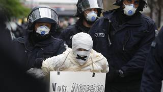 Police officers detain a person during an illegal demonstration against restrictions and measures to prevent the spread of COVID-19 in Berlin, Germany, on April 25.