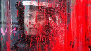 A police officer stands behind her riot shield covered in red paint during an International Women's Day march in Mexico City's main square, Sunday, March 8, 2020.