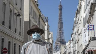 A man wears a mask to protect against the spread of the coronavirus walk in a street close to the Eiffel Tower in Paris, Sunday, April 26, 2020.