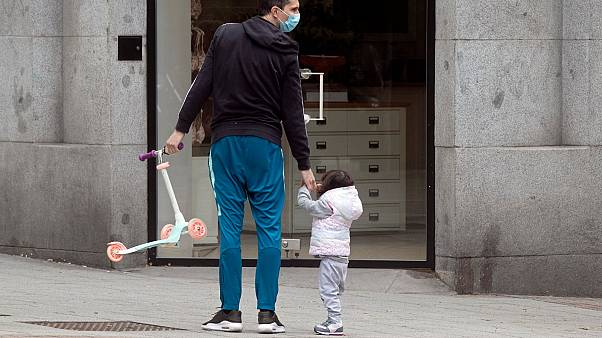 A man takes a young girl for a walk in Madrid, Spain, Sunday, April 26, 2020
