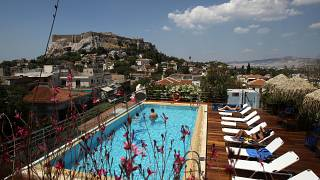 Tourists swim in a swimming pool on the roof of a hotel as the ancient Acropolis hill