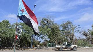 Fighters with Yemen's Southern Transitional Council (STC) drive a vehicle past a separatist flag