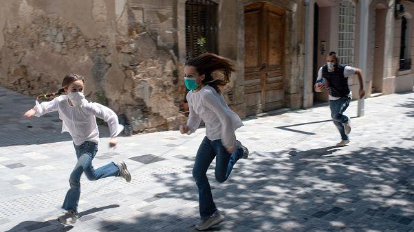 طفلان يركضان في شوارع برشلونة أمس الأحد بعدما سمحت السلطات للأطفال بالخروج لمدة زمنية محددة