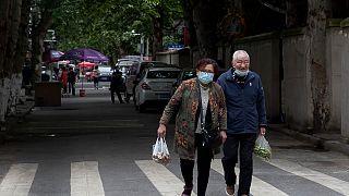 Çin'in Hubei bölgesindeki Vuhan şehrinde maske takmış yaşlı bir çift alışverişten dönüyor