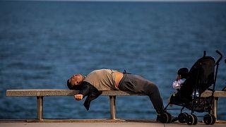 رجل مستلق على شاطئ في مدينة برشلونة الإسبانية - 2020/04/26