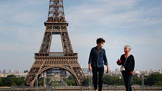 Paris'in Trocadero meydanında koronavirüsten korunmak için maske takmış iki kişi yürüyor