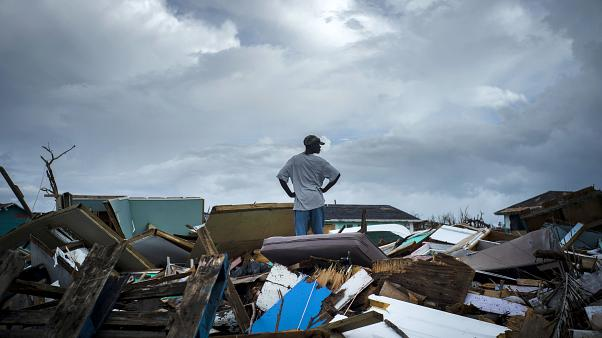 A man stands on the rubble of his home in the Haitian Quarter, after the passage of the Hurricane Dorian in Abaco, Bahamas, Monday, Sept. 16, 2019.