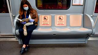 The signs reading 'Please do not sit here, respect social distancing' are visible on the seats in a metro train in Milan, Italy.