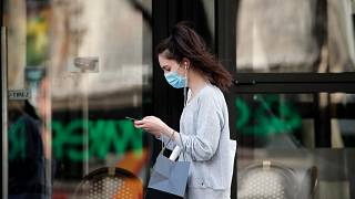 A woman wearing protective face mask walks looking at her phone past a closed restaurant during a nationwide confinement to counter the COVID-19, in Paris, April 20, 2020.