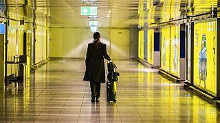 Eine Reisende schiebt ihren Koffer durch einen leeren Gang am Frankfurter Flughafen, 12. März 2020.