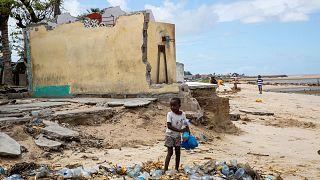 Uma criança recolhe garrafas de plástico na cidade moçambicana da Beira