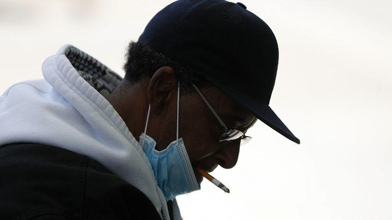Paul Sancya (AP) - Man pulls down a mask to smoke (2020)