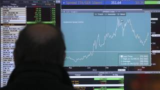 A man checks a monitor with stock exchange data in Milan, Italy,