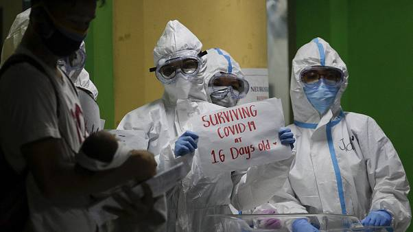 طاقم طبي في مستشفى في مانيلا يحيطون بطفل تعافى من مرض كوفيد-19 - 2020/04/28