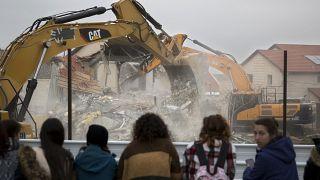 İsrailli yerleşimciler, Batı Şeria'daki bir evin yıkılışını izlerken