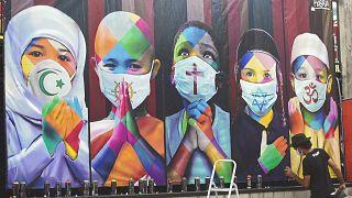 شاهد: جدارية في زمن كورونا تظهر ترابط وتوحد الأديان في مواجهة الوباء