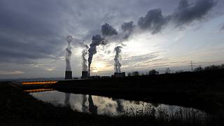 Smoke rises from chimneys of the Turow power plant located by the Turow lignite coal mine near the town of Bogatynia, Poland, Tuesday, Nov. 19, 2019.