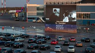 People sit in their cars watching a movie at a new drive-in cinema at the airport in Vilnius, Lithuania on April 29, 2020.