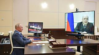Russian President Vladimir Putin listens to Prime Minister Mikhail Mishustin, displayed on TV screen on the right, during their meeting via teleconference - 30th April 2020