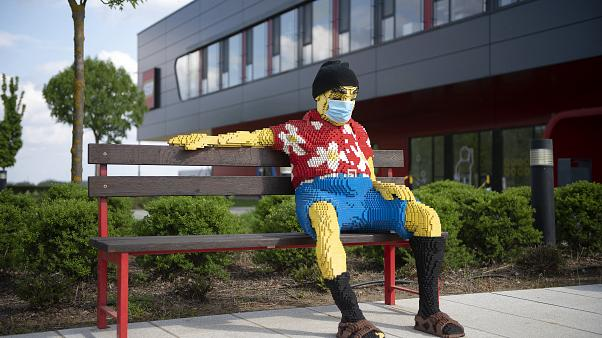 Padon ülő figura maszkban a nyíregyházi Lego-gyár előtt