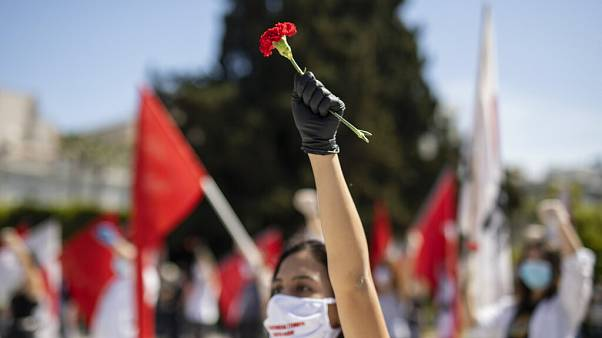 A protester from the communist party-affiliated PAME union wearing a mask to protect against coronavirus, holds a carnation during a May Day rally outside the Greek Parliament