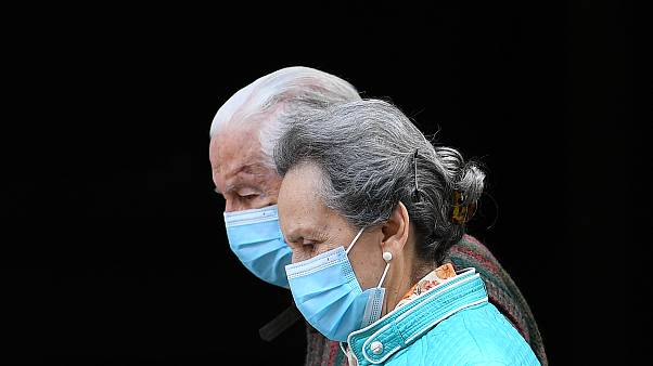 An elderly couple wearing face masks walks in Madrid on April 30, 2020 during a national lockdown to prevent the spread of the COVID-19 disease