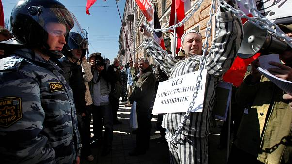 Officers cordon off an area near a performer staging a street protest during a Russian Communist Party march marking May Day in downtown St. Petersburg May 1, 2009.