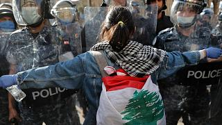 A protester confronts police during a demonstration against the deepening financial crisis, in Beirut, Lebanon, Tuesday, April 28, 2020
