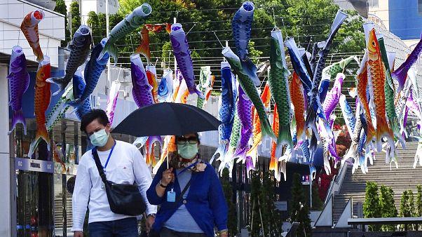 Maszkot viselő járókelők Japánban, 2020. május 2.