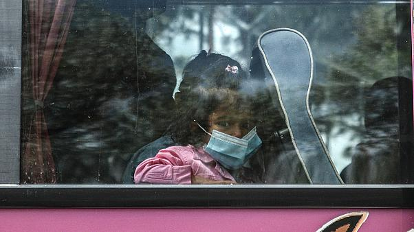 A child migrant looks from a bus window outside Moria camp on her way to the port of Mytilene, on the northeastern Aegean island of Lesbos, Greece, on May 3, 2020