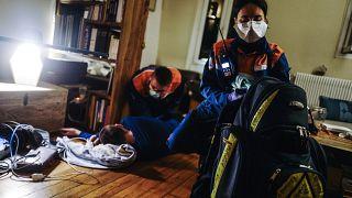 طاقم طبي يقدم المساعدة لمصاب بفيروس كورونا