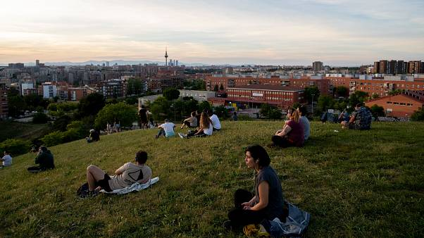 People sit in the Cerro del Tio Pio park in Madrid, Spain, after the lockdown was eased on the weekend