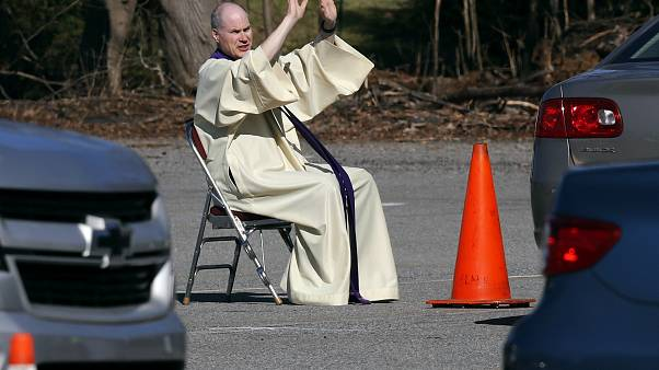 كاهن يرفع يديه خلال لقاءات اعتراف في مرآب للسيارات تزامنا مع انتشار وباء كوفيد-19 في الولايات المتحدة - 2020/04/06