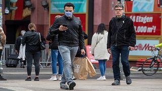 رجل يرتدي قناع وجه يخرج من مركز تسوق في برلين في 29 أبريل 2020 وسط انتشار فيروس كورونا