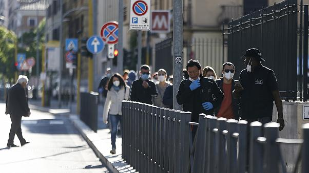 People crowd a street in Rome, Monday, May 4, 2020. Italy began stirring again Monday after a two-month coronavirus shutdown