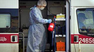 عامل طبي يرتدي معدات واقية يرش مطهراً في سيارة إسعاف، مستشفى بوكروفسكايا في سان بطرسبرج، روسيا