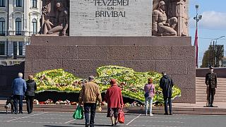 People arrive to lay a wreath in front of the Monument of Freedom to mark the 30th anniversary of the restoration of independence of the Republic of Latvia on May 4, 2020
