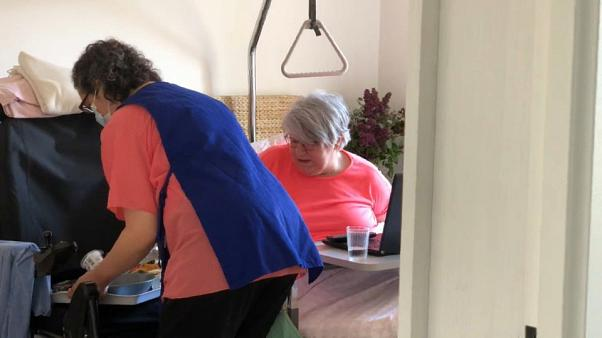 Caregiver Cecile Aime serves Joëlle Brusset breakfast, the 62-year-old has a disabling neurological disorder